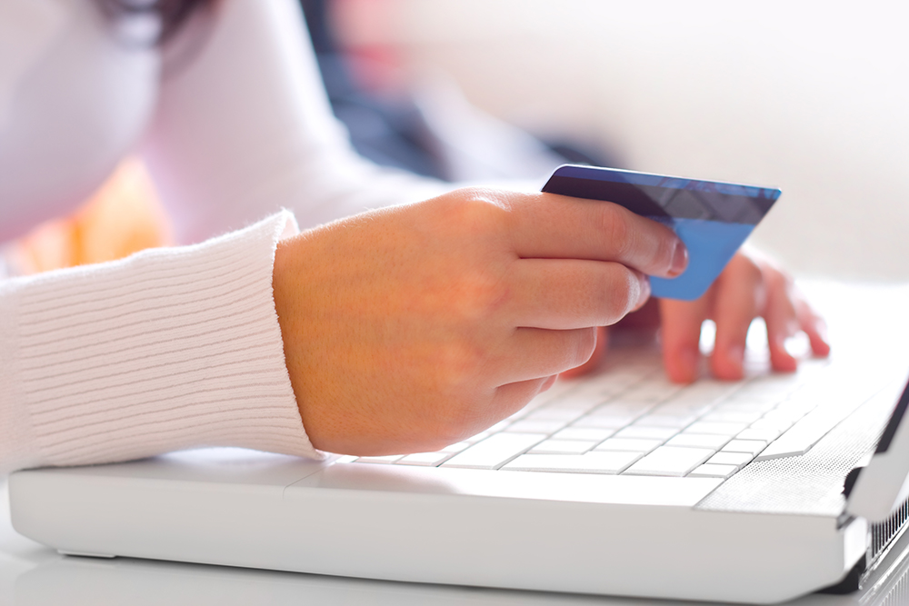 Young woman with credit card. On-line shopping on the internet using a laptop.